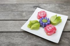 Colorful Thai style layer cake in flower shape. On wood table background Stock Image