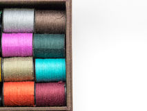 The colorful thread consists. Of orange, yellow, pink and green in a brown fabric box. On a white background.  background Stock Images