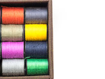 The colorful thread consists. Of orange, yellow, pink and green in a brown fabric box. On a white background.  background Stock Image
