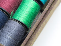 The colorful thread consists. Of orange, yellow, pink and green in a brown fabric box. On a white background.  background Royalty Free Stock Photo