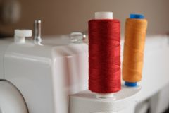 Colorful thread spools used in fabric and textile industry. Colored thread coils mounted on a pin of a sewing machine Stock Photo