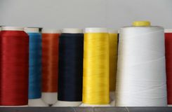 Colorful thread in the thread roll, yellow color, red, white, blue, orange and dark blue. Through the use already from sewing garment and prepare to use again stock photography