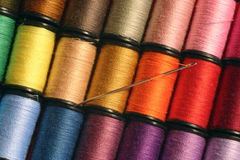 Colorful Threads. A needle at rest among colorful sewing threads Royalty Free Stock Photography