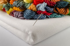 Colorful threads for embroidery on canvas with needle Royalty Free Stock Photos