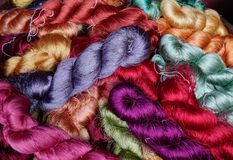 Colorful threads of Thai silk in a basket royalty free stock photo