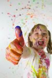 Colorful Thumb Up. A young child giving a thumbs up covered in colorful paint Stock Photography