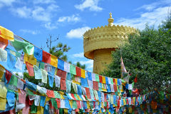 Colorful tibetian flags and biggest buddhist wheel in the world. On the background of blue sky in Shangri-La, China stock photo