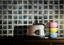 Colorful tiffin carrier and toaster on wooden cupboard Royalty Free Stock Photo