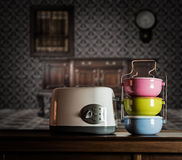 Colorful tiffin carrier and toaster on wooden cupboard Stock Photos