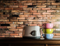 Colorful tiffin carrier and toaster on wooden cupboard Royalty Free Stock Photos