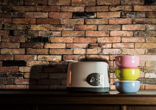 Colorful tiffin carrier and toaster on wooden cupboard with vint Stock Photography