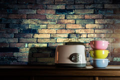 Colorful tiffin carrier and toaster on wooden cupboard with vint Stock Photos