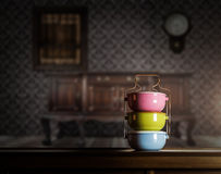 Colorful tiffin carrier on wooden cupboard royalty free stock photography