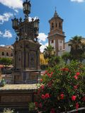 Colorful tiled seating, fountain with red flowers and church. Monumental colorful tiled fountain at the center of the the Plaza Alta with the Iglesia de Nuestra Stock Photos