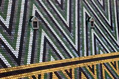 Colorful tiles and windows on Stephansdom roof Vienna Austria. Closeup of triangle pattern multi colored glazed tiles with two windows on the steep pitch roof of Stock Photography