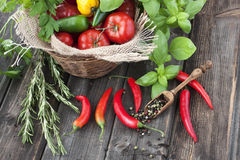 Colorful  tomatoes in a basket and pepper on wooden background Royalty Free Stock Photos