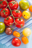 Colorful tomatoes over blue napkin Stock Photo