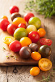Colorful tomatoes over wooden background Royalty Free Stock Photos