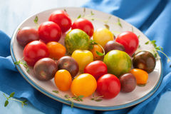 Colorful tomatoes in plate on blue background Stock Photos