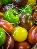Colorful tomatoes on sale. Fresh red, brown, yellow and green ripe tomatoes in wooden baskets on sale on a farmers Borough Market in London Royalty Free Stock Images