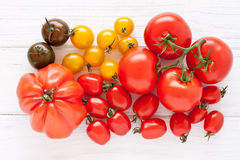Colorful tomatoes. On a white wooden board Royalty Free Stock Photo