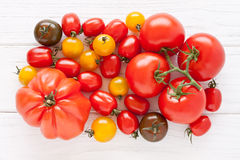 Colorful tomatoes. On a white wooden board Stock Photo