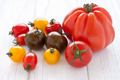 Colorful tomatoes. On a white wooden board Stock Photos