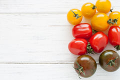Colorful tomatoes. On a white wooden board Royalty Free Stock Images