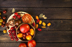 Colorful tomatoes on wooden background. top view. dark wood table Royalty Free Stock Photo