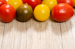 Colorful tomatoes on a wooden board  with text space Stock Photo