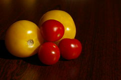 Colorful tomatos. Close up tomates in yellow and red on wood Royalty Free Stock Images