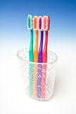 Colorful Toothbrushes. A view of colorful toothbrushes in a cup, on blue studio background Stock Photos