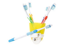 Colorful toothbrushes in cup with dental floss Stock Image