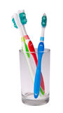 Colorful toothbrushes in a glass on background. Stock Photos