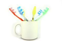 Colorful Toothbrushes In A White Mug Royalty Free Stock Photography