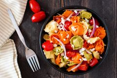 Colorful tortellini pasta salad, overhead scene on dark wood Stock Photo