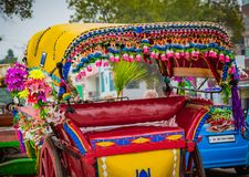 Colorful tourist rickshaw with tassels and flowers awaits the next tourist passenger. In India royalty free stock images