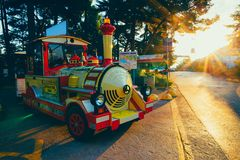 The colorful tourist train offers the pleasure rides along the promenade. Summer holiday by the sea. The colorful tourist train offers the pleasure rides along Stock Photos