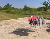 Colorful towels are being hung on bar for drying. Colorful wet towels are being hung on bar for drying Royalty Free Stock Images