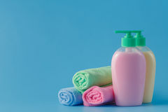 Colorful towels and liquid soap over blue background Royalty Free Stock Photos