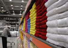 Colorful towels on shelf in stor. Colorful towels on shelf and man with cart Royalty Free Stock Image