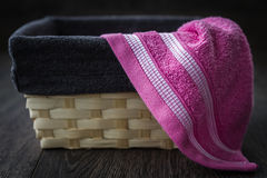 Colorful Towels in Wicker Basket. Towels of different colors in wicker basket on brown wooden background stock photos