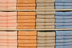 Colorful towels with wicker basket on shelf of rack background Stock Photo