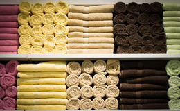 Colorful towels with wicker basket on shelf of rack background Stock Images
