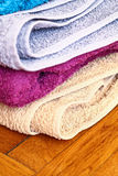 Colorful towels on wooden floor.  Royalty Free Stock Photos