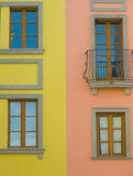 Colorful townhouses details. Colourful facades of two townhouses: left one yellow with windows, right one pinkish with a window and a classical balcony; blue sky Royalty Free Stock Images