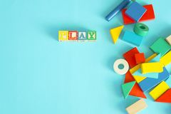 Colorful toy blocks flat lay on blue background. Variety of colorful toy blocks with word `Play` on blue background, flat lay Stock Photo