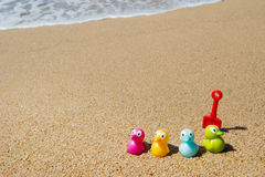Colorful toy ducks at beach royalty free stock images
