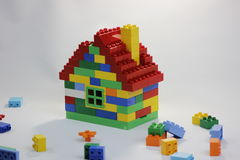 Colorful toy house with bricks in mess Stock Images