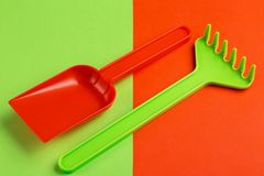 Colorful toy spade and rake on bright background. Copy space royalty free stock photography